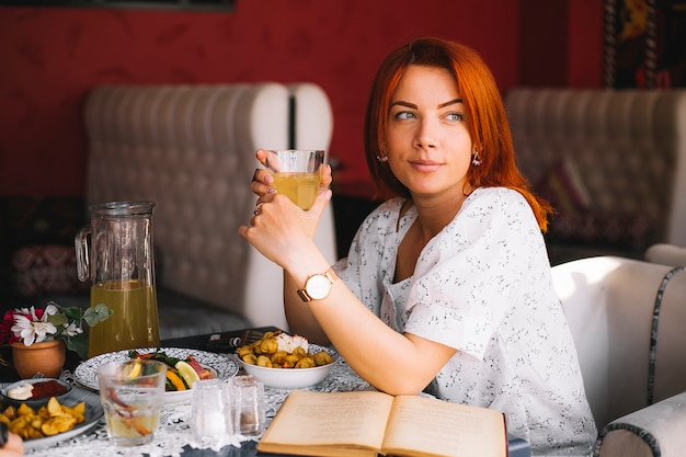 Mujer pelirroja almorzando en el restaurante