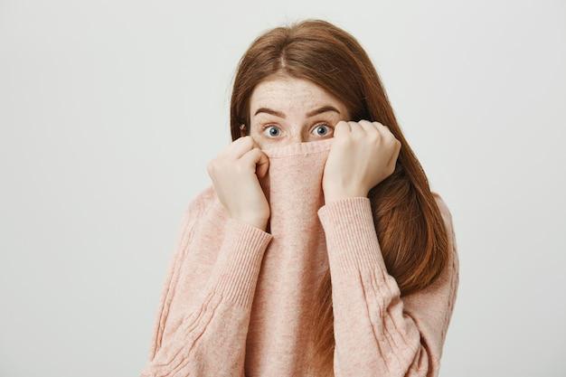 Mujer pelirroja asustada escondiendo la cara en el cuello del suéter, temblando