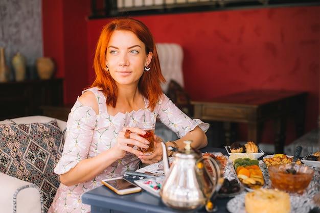 Mujer pelirroja bebiendo té en el restaurante