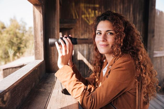 Mujer pelirroja con binoculares