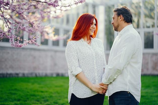 Mujer pelirroja en una blusa blanca de pie en un parque soleado de verano con su novio
