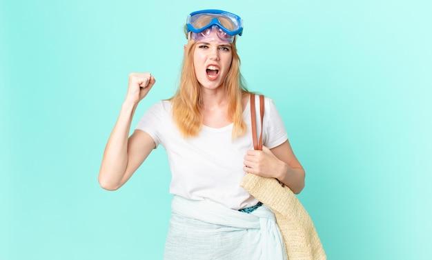 Mujer pelirroja bonita gritando agresivamente con una expresión de enojo con gafas. concepto de verano