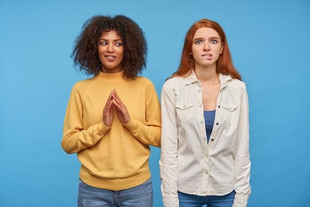 Mujer pelirroja bonita joven nerviosa mordiendo su labio inferior y mirando con preocupación mientras está de pie sobre la pared azul con su amiga de piel oscura rizada de pelo oscuro encantadora positiva
