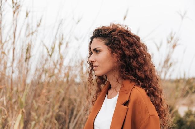 Mujer pelirroja en el campo de trigo mirando a otro lado