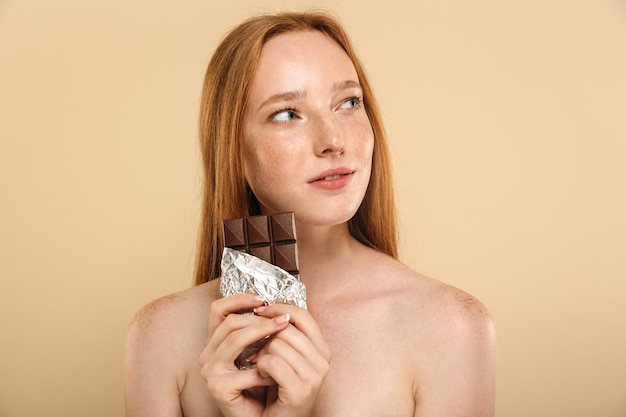 Mujer pelirroja comiendo chocolate.