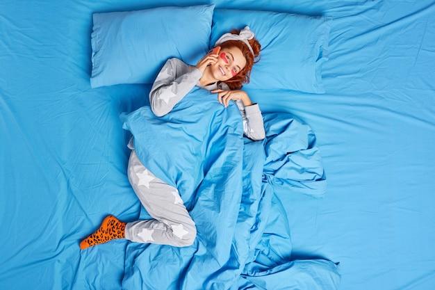 La mujer pelirroja complacida usa un pijama suave aplica parches de colágeno debajo de los ojos, habla a través del teléfono móvil mientras está acostada en la cama y disfruta de los chismes de la mañana y el día libre con mi mejor amiga desde arriba