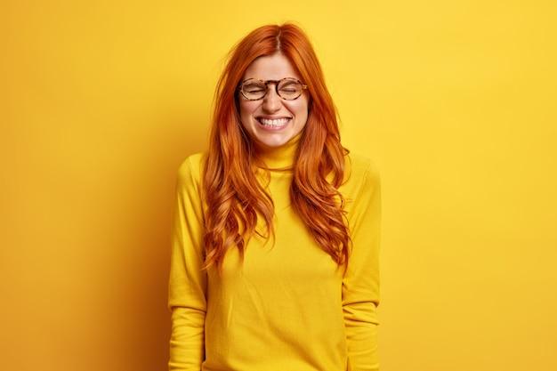 Mujer pelirroja despreocupada con expresión de alegría se ríe mientras escucha una anécdota divertida, cierra los ojos y muestra dientes blancos vestida con un cuello alto informal.