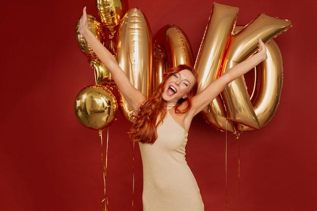 Mujer pelirroja en elegante vestido posando emocionada con globos dorados en rojo