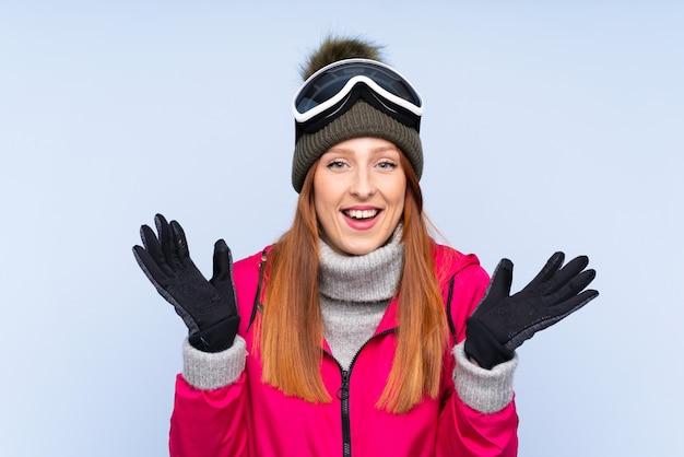 Mujer pelirroja esquiador con gafas de snowboard sobre pared azul aislado riendo