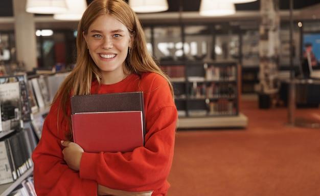 Mujer pelirroja estudiando, sosteniendo libros en la librería y sonriendo.