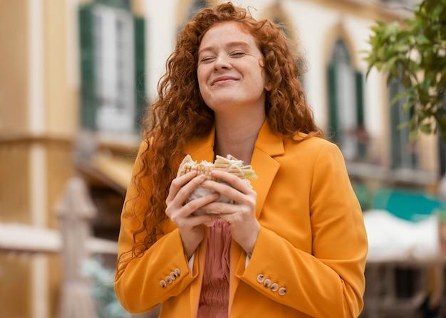 Mujer pelirroja feliz comiendo algo de comida en la calle