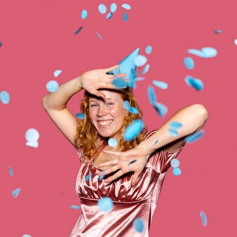 Mujer pelirroja feliz lanzando confeti