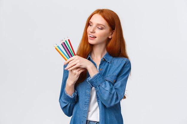 Mujer pelirroja guapa creativa y hábil en camisa de mezclilla, recogiendo lápices de colores, sonriendo pensando qué dibujar, creando obras de arte, de pie fondo blanco pensativo.