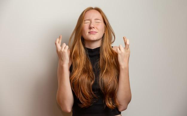 Mujer pelirroja infeliz dando pulgares abajo gesto mirando con expresión negativa y desaprobación. pared amarilla