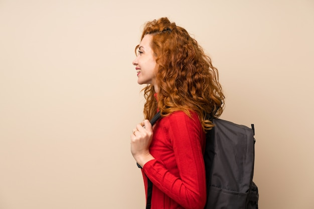 Mujer pelirroja con jersey de cuello alto con mochila
