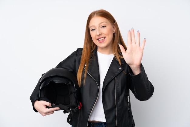 Mujer pelirroja joven con un casco de moto sobre pared blanca aislada saludando con la mano con expresión feliz