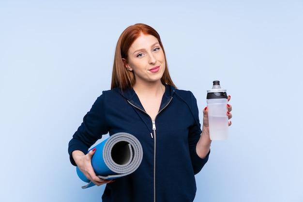 Mujer pelirroja joven deporte con botella de agua deportiva y con una estera