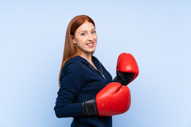 Mujer pelirroja joven deporte sobre fondo azul aislado con guantes de boxeo