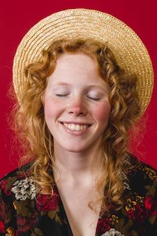 Mujer pelirroja joven con los ojos cerrados y sonriendo