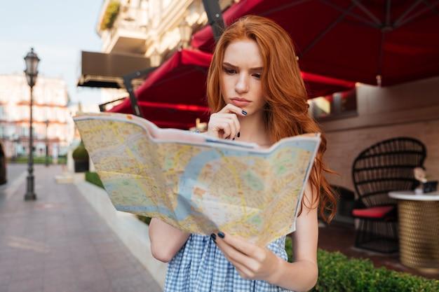 Mujer pelirroja joven pensativa mirando un mapa guía