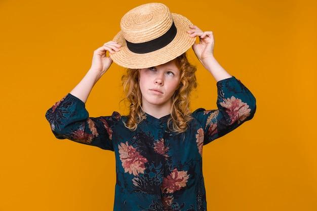 Mujer pelirroja joven que pone en el sombrero beige