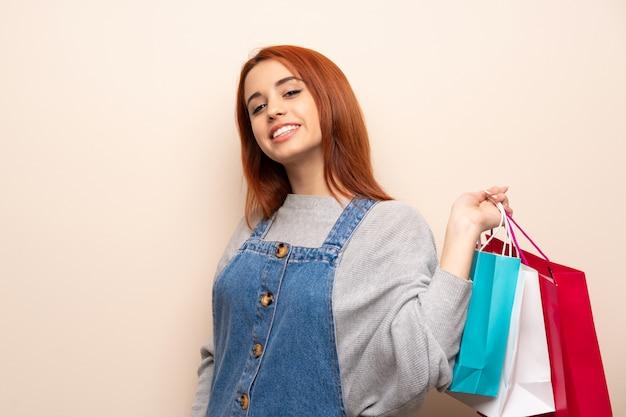 Mujer pelirroja joven que sostiene muchas bolsas de compras