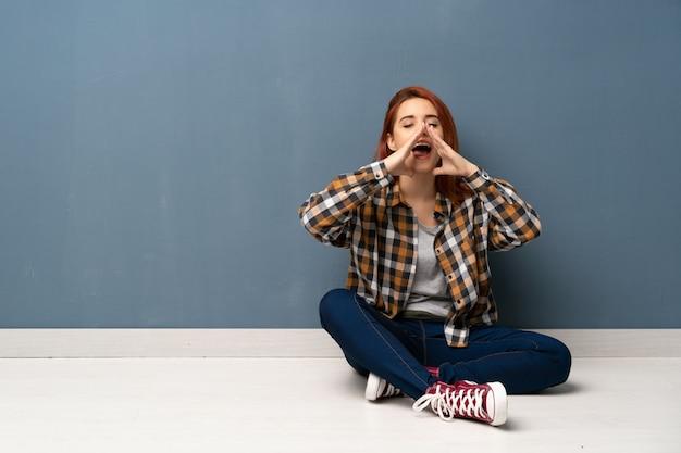 Mujer pelirroja joven sentada en el piso gritando y anunciando algo
