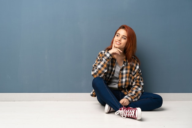 Mujer pelirroja joven sentada en el piso pensando en una idea mientras mira hacia arriba