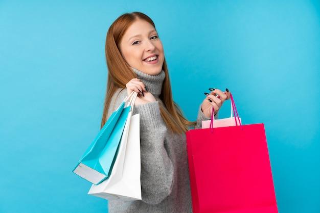 Mujer pelirroja joven sosteniendo bolsas de compras y sonriendo