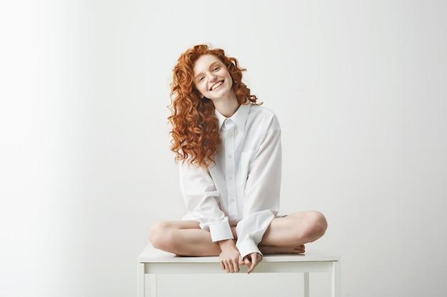 Mujer pelirroja joven tierna en camisa sonriendo sentado en la mesa posando.