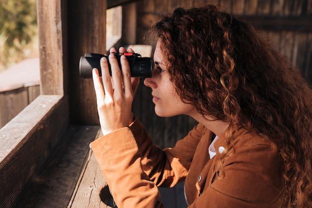 Mujer pelirroja de lado mirando a través de binoculares