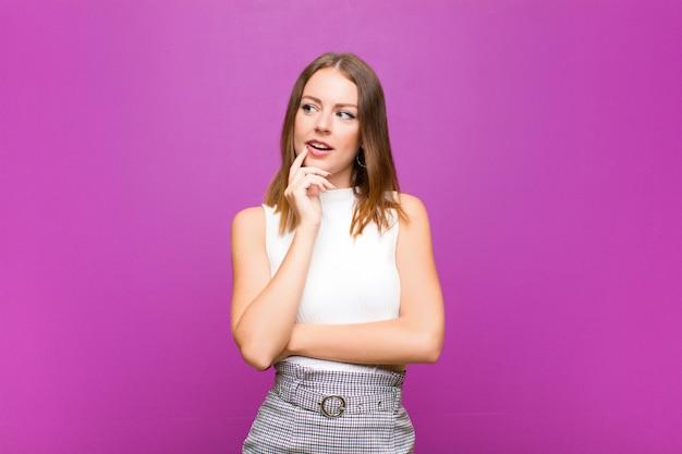 Mujer pelirroja con mirada sorprendida, nerviosa, preocupada o asustada, mirando hacia el lado hacia el espacio de la copia en la pared púrpura