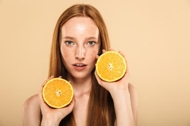 Mujer pelirroja con naranja.