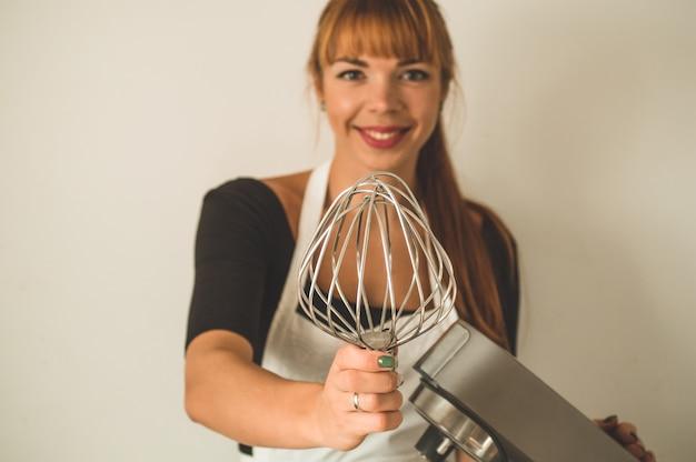 Mujer pelirroja pastelera sostiene batidora eléctrica del procesador de alimentos