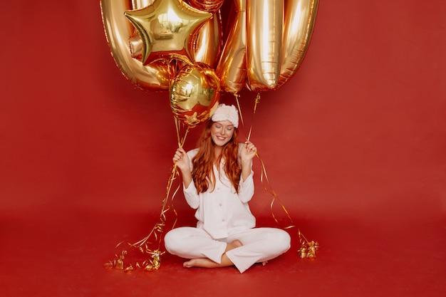 Mujer pelirroja en pijama y máscara para dormir posando emocionada sosteniendo globos dorados en rojo