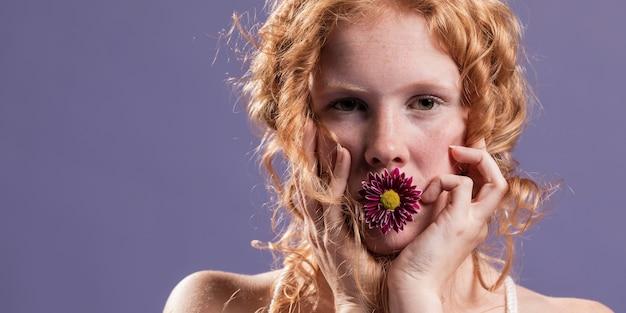 Mujer pelirroja posando con un crisantemo en la boca y copia espacio