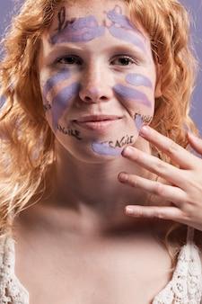 Mujer pelirroja que cubre palabras con pintura
