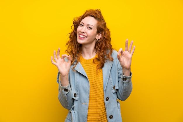 Mujer pelirroja sobre amarillo aislado que muestra un signo aceptable con los dedos