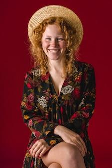 Mujer pelirroja con sombrero sonriendo y sentada con las piernas cruzadas