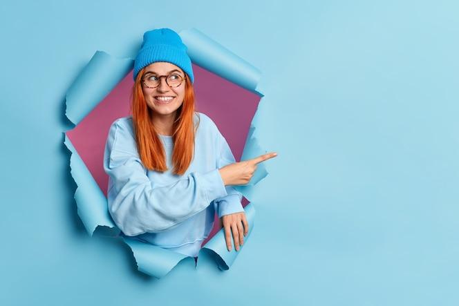 La mujer pelirroja sonriente complacida señala con el dedo en el espacio de la copia muestra una oferta especial o una venta de compras recomienda un buen descuento vestida con un elegante atuendo azul tiene un estado de ánimo feliz que se rompe a través del agujero del papel