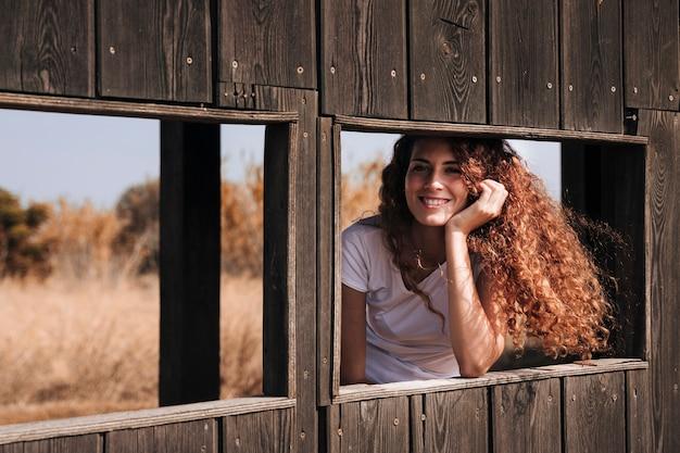 Mujer pelirroja sonriente dentro de un refugio