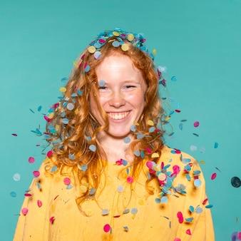 Mujer pelirroja sonriente de fiesta con confeti en el pelo