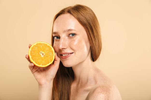 Mujer pelirroja sonriente sosteniendo naranja. mirando la cámara.