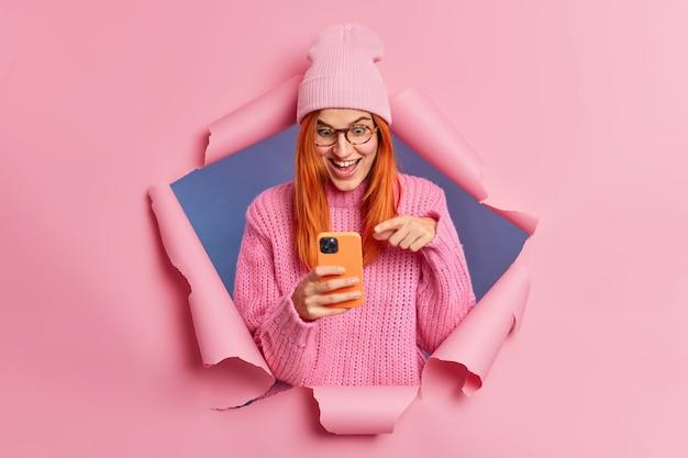 La mujer pelirroja sorprendida alegre apunta a la pantalla del teléfono inteligente reacciona ante los grandes descuentos en la tienda en línea, se ríe feliz y mira algo increíble, viste ropa elegante.