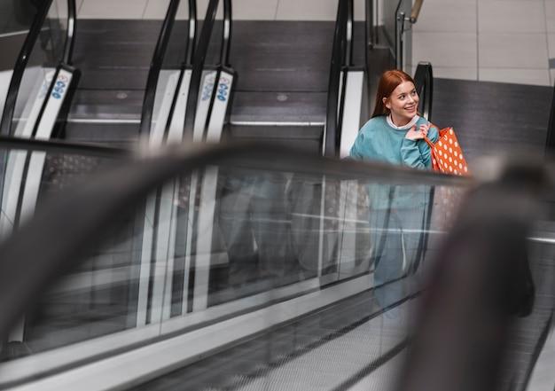 Mujer pelirroja subir escaleras mecánicas