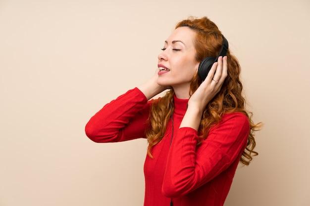 Mujer pelirroja con suéter de cuello alto escuchando música con auriculares