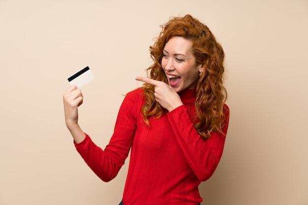 Mujer pelirroja con suéter de cuello alto sosteniendo una tarjeta de crédito
