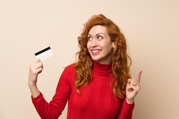 Mujer pelirroja con suéter de cuello alto con una tarjeta de crédito
