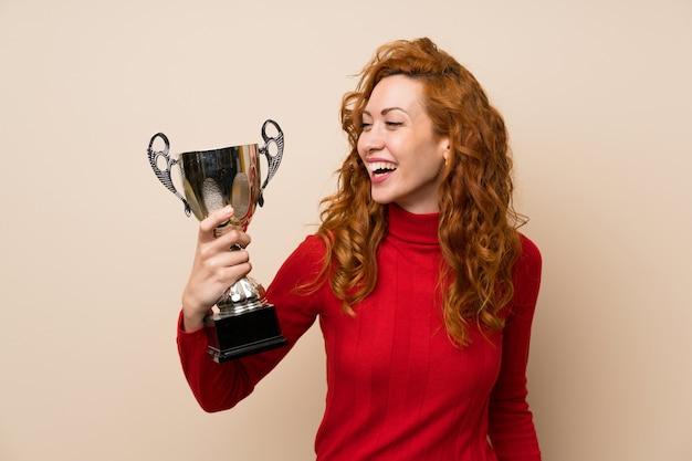 Mujer pelirroja con suéter de cuello alto con un trofeo