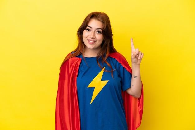Mujer pelirroja de superhéroe aislada sobre fondo amarillo apuntando con el dedo índice una gran idea